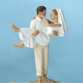 La figurine marié portant la mariée plage
